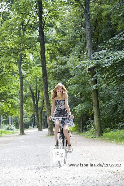 Hübsche blonde Frau auf dem Fahrrad im Park.