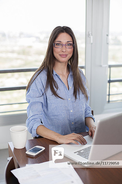 Pretty brunette woman with laptop smiling at camera