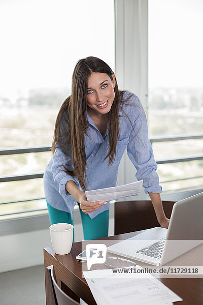 Brunette woman with bill and laptop smiling at camera