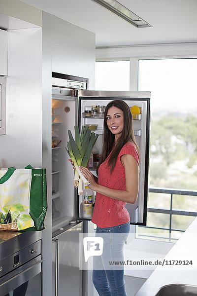 Hübsche Frau mit Lauch am Kühlschrank