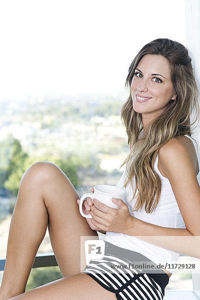 Frau sitzt in der Küche und trinkt einen Kaffee mit einem Lächeln vor der Kamera.