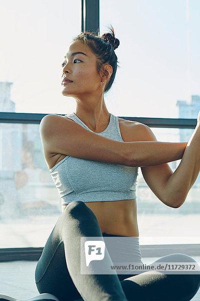Junge Frau im Fitnessstudio  Stretching