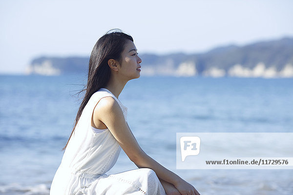 Young Japanese woman in a white dress by the sea  Chiba  Japan