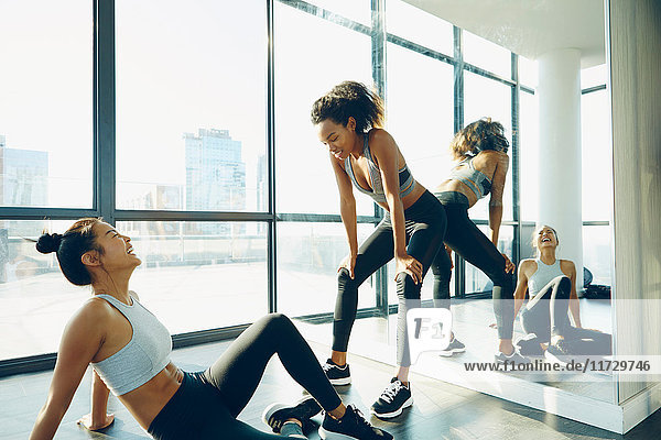 Two young women in gym  taking a break from workout