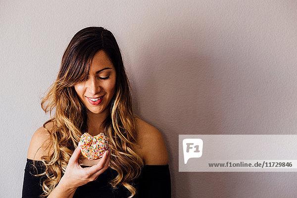 Junge Frau mit langen blonden Haaren hält Donutloch