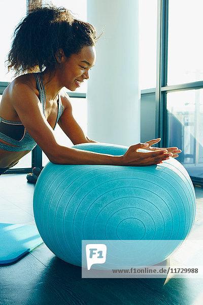 Junge Frau trainiert im Fitnessstudio mit einem aufblasbaren Übungsball