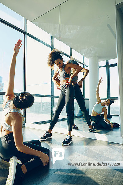 Zwei junge Frauen trainieren im Fitnessstudio und dehnen sich