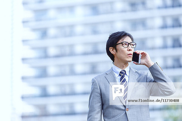 Japanese businessman on the phone downtown Tokyo  Japan