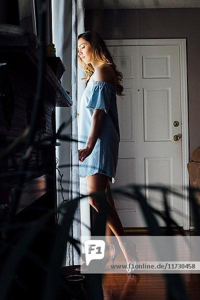 Anspruchsvolle junge Frau  die durch ein Fenster blickt