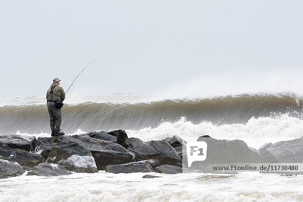 Man fishing from rocks in stormy ocean waves  Long Beach  New York  USA