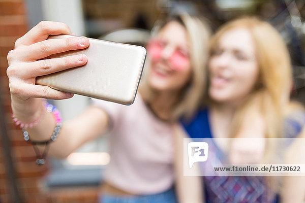 Zwei Freundinnen  im Freien  Selbsthilfe  mit Smartphone