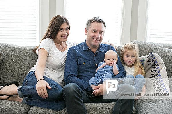 Porträt einer auf dem Sofa sitzenden Familie