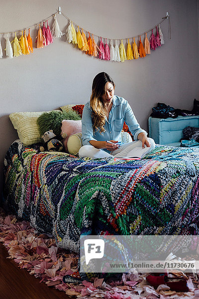 Junge Frau im Schneidersitz auf schäbig-schickem Bett schreibt in Notizbuch