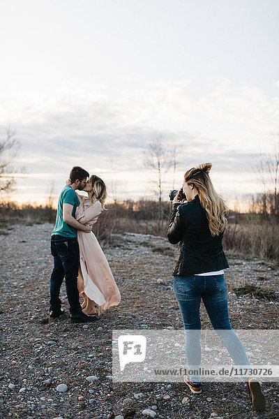 Photographer photographing couple  couple kissing in rural setting