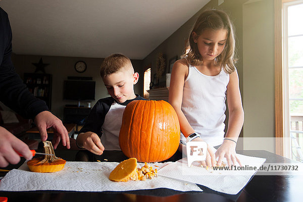 Father and children carving pumpkin