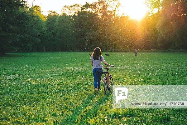 Frau geht Fahrrad auf Gras