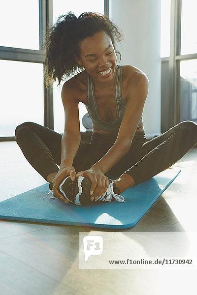 Junge Frau  die im Fitnessstudio trainiert  Stretching