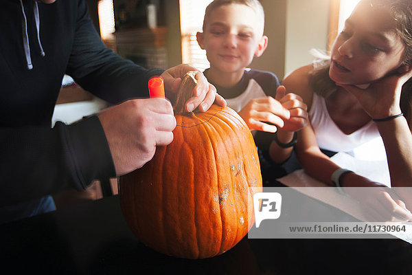 Father and children pumpkin carving