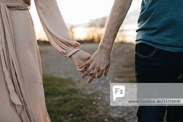 Couple holding hands  outdoors  mid section  close-up