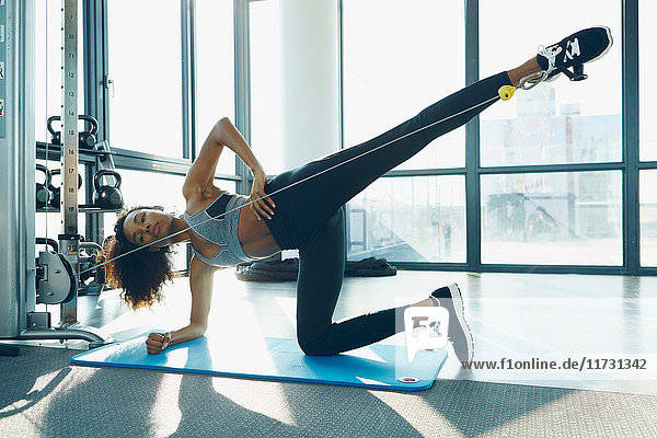 Junge Frau  die im Fitnessstudio trainiert und Fitnessgeräte benutzt