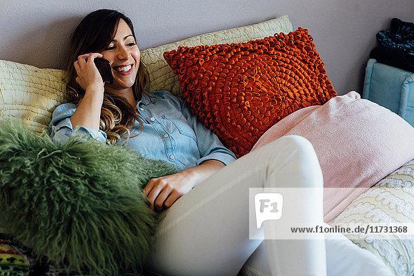 Junge Frau auf schäbig-schickem Bett liegend telefoniert mit Smartphone