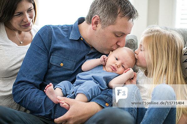Familie sitzt auf dem Sofa  Vater und junges Mädchen küssen den kleinen Jungen