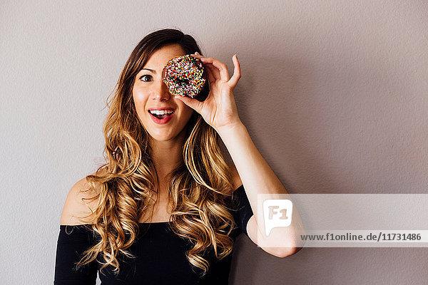 Porträt einer jungen Frau mit langen blonden Haaren  die ein Donutloch über dem Auge hält