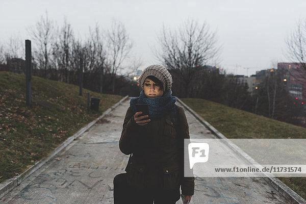 Backpackerin geht in der Abenddämmerung im Stadtpark spazieren und schaut auf ihr Smartphone