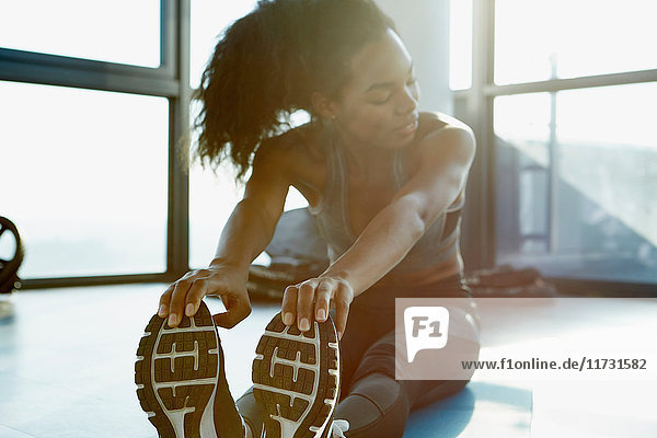 Junge Frau übt im Fitnessstudio  dehnt sich  berührt die Zehen