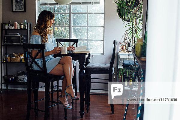 Anspruchsvolle junge Frau liest Buch bei Tisch