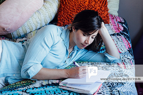 Junge Frau liegt auf schäbig-schickem Bett und schreibt in einem Notizbuch