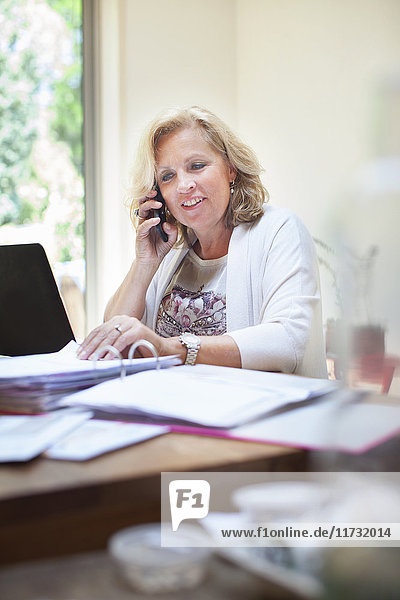 Mature woman sitting at table  looking through paperwork  using smartphone
