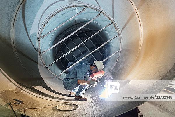 Männlicher Schweißer  der in einem Industrierohr in einer Kranfabrik arbeitet  China