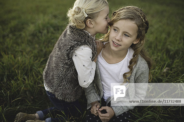 Young girl whispering in sister's ear  outdoors