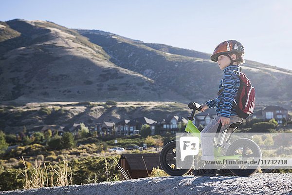 Boy sitting on balance bike in front of mountain  Draper cycle park  Missoula  Montana  USA