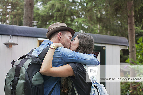 Romantic couple kissing on cabin porch
