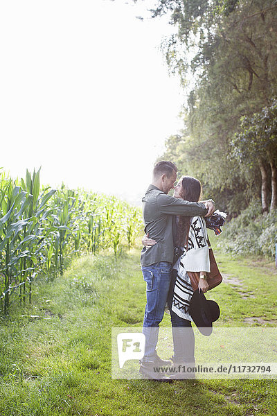 Romantic couple hugging each other in field