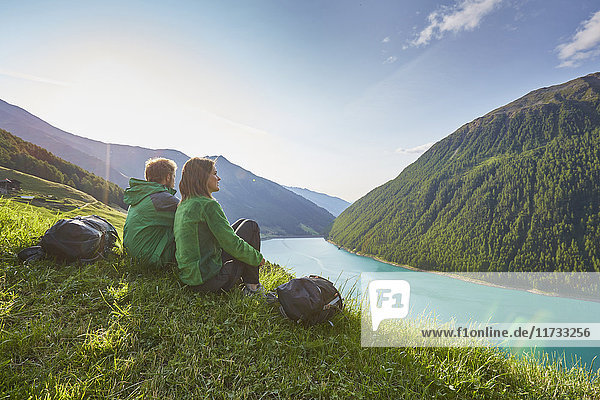 Young couple sitting looking out over Vernagt reservoir and Finailhof farmhouse  Val Senales  South Tyrol  Italy