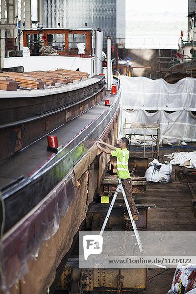 Arbeiter auf Trittleiter  der das Boot in der Werftwerkstatt überprüft