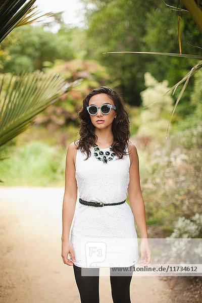 Junge Frau in weißem Kleid und Sonnenbrille im Park