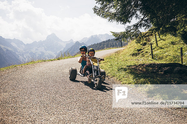Mother and son wearing helmets riding go cart on curved road  looking at camera mouth open  Bludenz  Vorarlberg  Austria