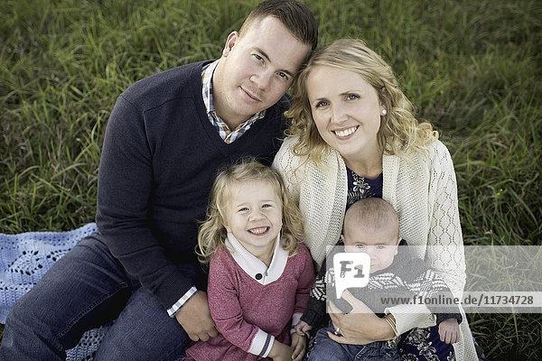 Porträt eines Paares mittlerer Erwachsener auf Picknickdecke mit Tochter und Junge