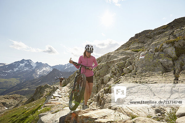 Young couple with mountain bikes on path at Val Senales Glacier  Val Senales  South Tyrol  Italy