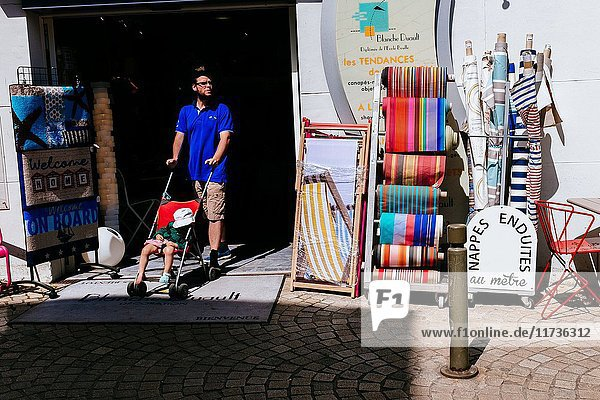Young man with baby in stroller coming out from fabrics store. Vannes  Brittany  France.