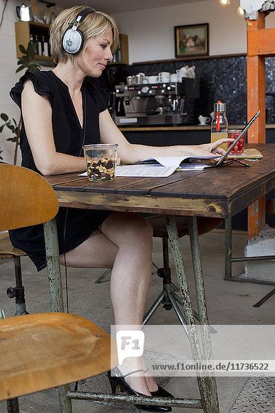 Mittlere erwachsene Frau  die im Café arbeitet und Kopfhörer trägt