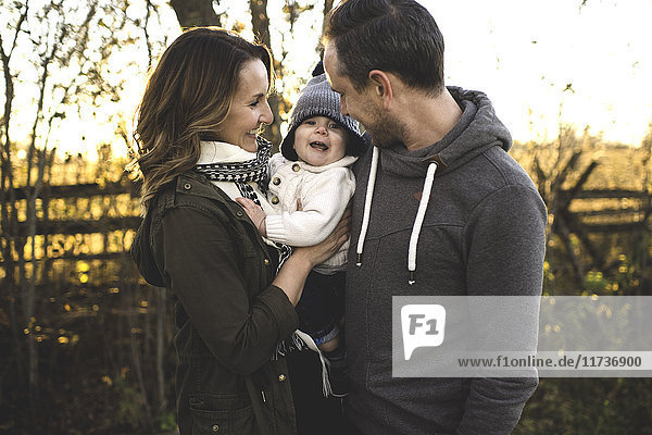 Couple holding baby boy outdoors in autumn  looking at camera smiling