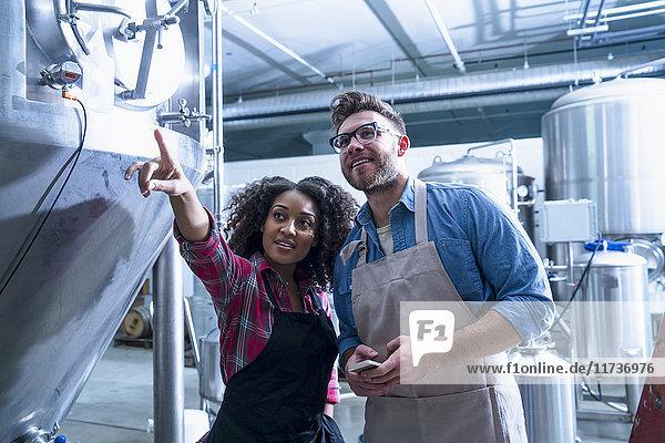 Brauereikollegen am konischen Gärtank  zeigen lächelnd nach oben blickend