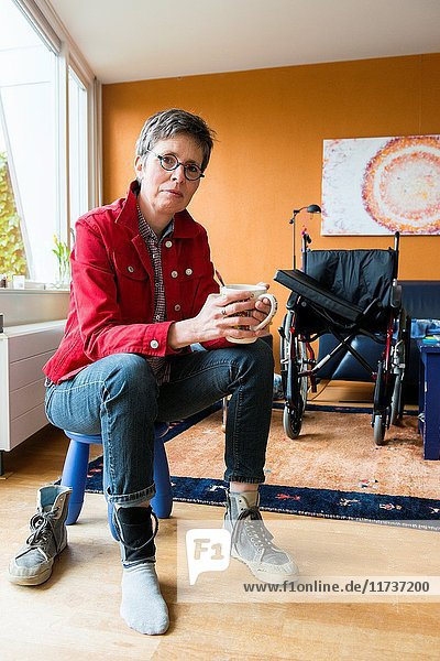 Tilburg  Netherlands. Living room portrait of a mature adult woman suffering from Multiple Sclerosis sitting besides her unused wheelchair.