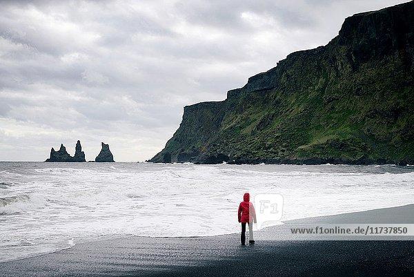 Iceland  Sudurland region  Vik i Myrdal  Vik beach  woman on the black sand beach and Reynisdrangur sea stacks  Model Released