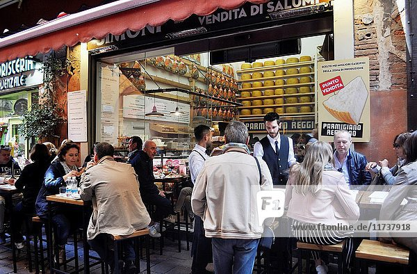 Bologna  Italy: tourists eating at a cold cuts and Parmesan cheese along via Pescherie Vecchie